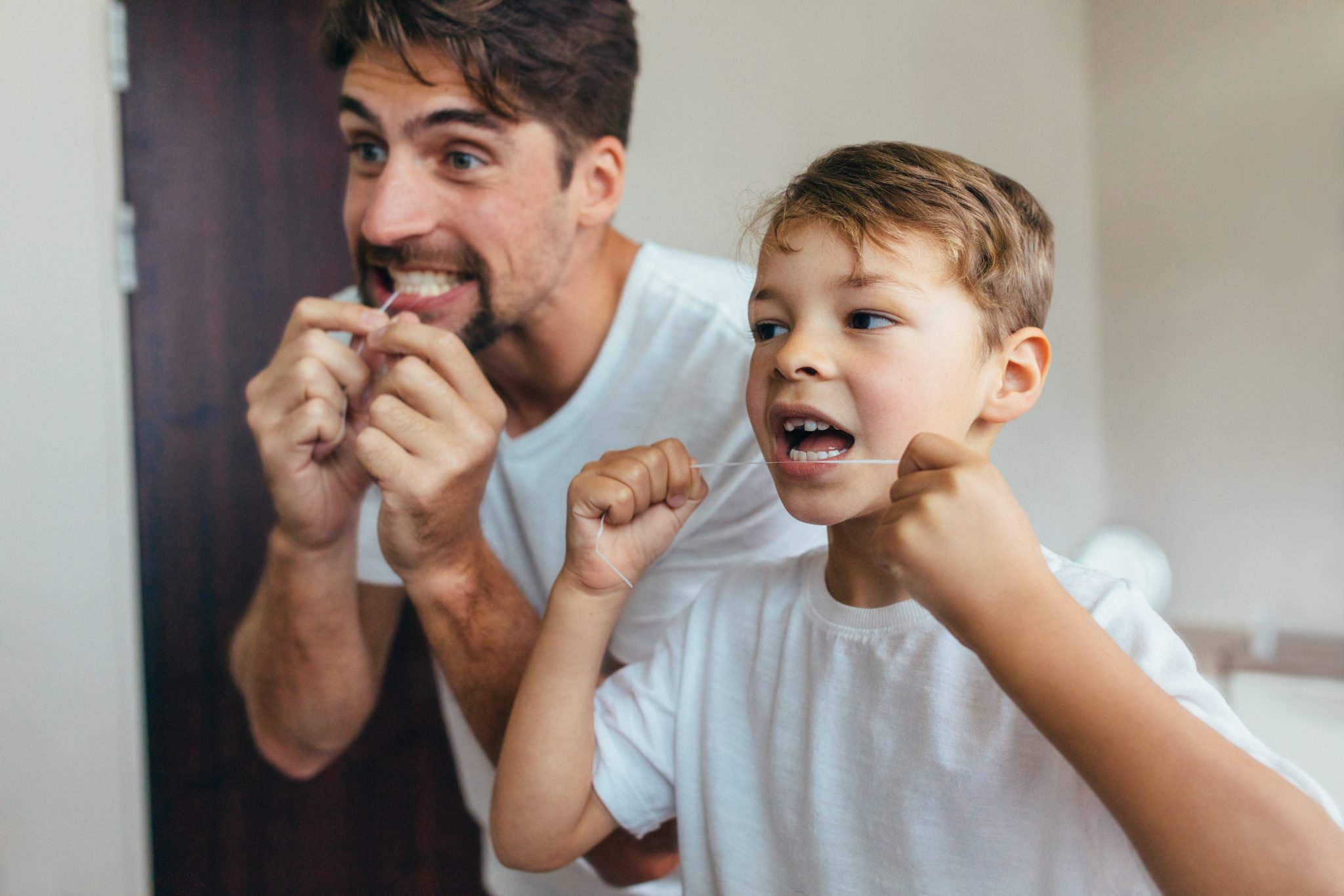 Father And Son Cleaning Teeth With Dental Floss